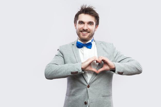 カジュアルな灰色のスーツと青い蝶ネクタイで幸せなハンサムなひげを生やした男は、心または愛のジェスチャーで立って、歯を見せる笑顔でカメラを見ています。明るい灰色の背景に分離された屋内スタジオショット。