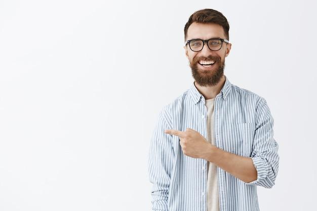 Uomo barbuto bello felice che posa contro il muro bianco