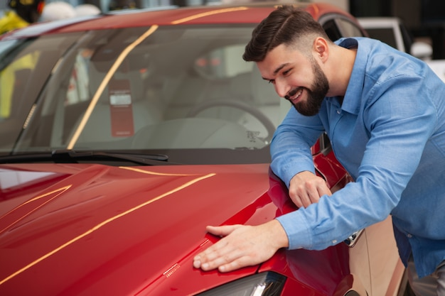 Happy handsome bearded man smiling, examining beautiful red automobile on sale at car dealership, copy space