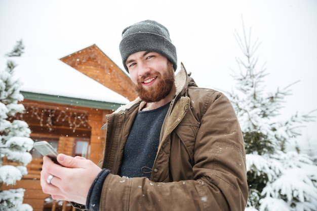 Happy handsome bearded man with cell phone standing near