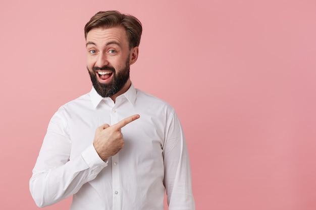 白いシャツを着て、幸せなハンサムなひげを生やした若い男。素晴らしいニュースを伝えたい。大きく笑って、ピンクの背景の上に隔離された右側のコピースペースを指してあなたの注意を引きます。