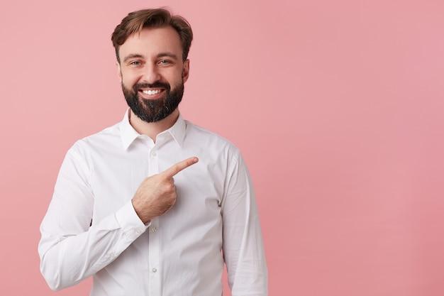 白いシャツを着て、幸せなハンサムなひげを生やした若い男。クールなニュースを伝えたい。大きく笑って、右側のコピースペースを指して注意を引きます。ピンクの背景に分離。