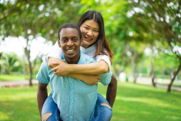 Happy handsome black guy carrying asian girlfriend on his back while they walk