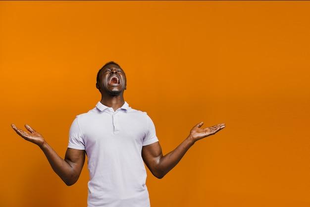 행복한 잘생긴 흑인 남자가 주황색 배경에서 온라인 베팅에서 이깁니다. 아프리카인이 상을 받았습니다. 가정 검역 개념에서 온라인 작업.
