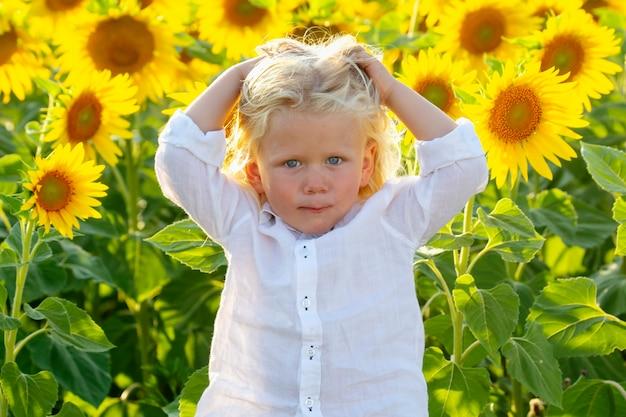 긴 금발 머리를 가진 행복한 잘생긴 소년이 피는 해바라기 밭에 서 있다