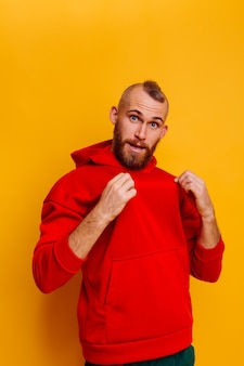 Happy handsome brutal bearder man wearing warm red winter trendy fleece hoodie