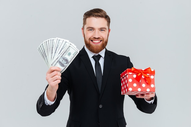 Happy handsome business man in suit holding gift and money in hands. isolated gray background