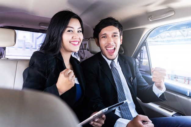 Happy handsome businessman and business woman sitting in luxury limousine car, working on laptop computer, works anytime and anywhere concept.