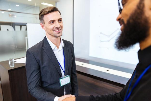 オフィスで若いひげを生やしたアフリカの同僚と握手幸せなハンサムなビジネスマン