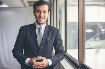 Happy handsome businessman standing and smiling in office