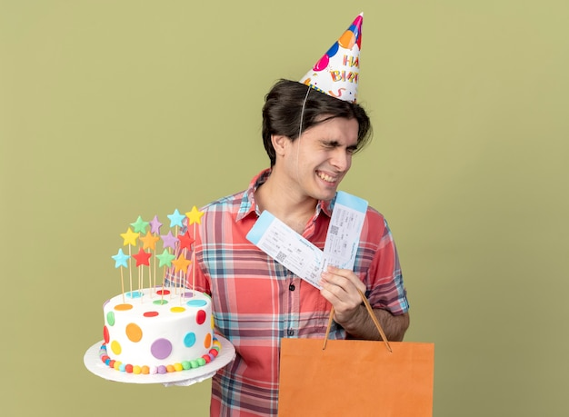 Happy handsome caucasian man wearing birthday cap holds paper shopping bag air tickets and birthday cake