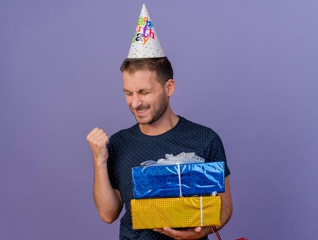생일 모자를 쓰고 행복 잘 생긴 백인 남자가 주먹을 유지하고 복사 공간이 보라색 배경에 고립 된 선물 상자를 보유하고 있습니다.