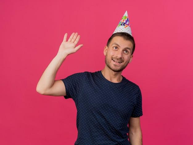 생일 모자를 쓰고 행복 잘 생긴 백인 남자는 복사 공간이 분홍색 배경에 고립 제기 손으로 스탠드