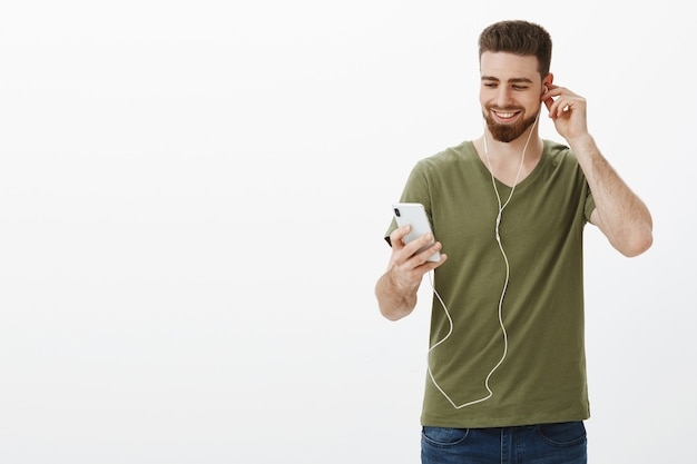 Happy handsome caucasian man with beard in t-shirt putting on earphone as looking pleased at smartphone smiling, picking song to listen on road to work listening music over white wall