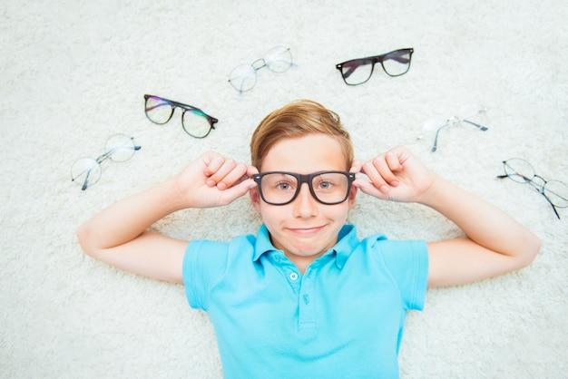 Счастливый красивый ребенок мальчик примеряет очки.