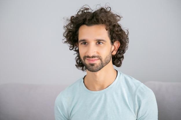 행복 잘 생긴 곱슬 머리 젊은 남자 캐주얼 티셔츠를 입고 집에서 소파에 앉아 멀리보고 웃 고. 남성 초상화 개념