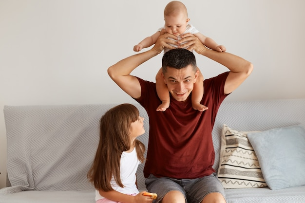 Happy handsome dark haired man wearing casual style clothing posing at home together with his kids, cute infant baby on dad's shoulders, family expressing happiness.
