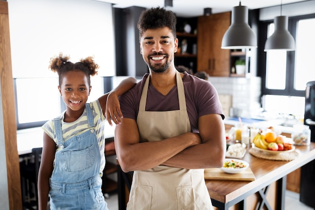 幸せなハンサムな父と台所の子供たち。健康食品、家族、料理のコンセプト