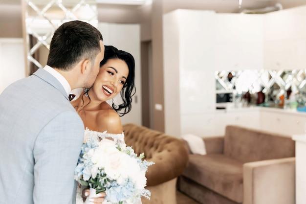Счастливый красивый жених и блондинка красивая невеста в белом платье, обнимая под дугой