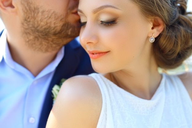 Happy handsome groom and beautifyl bride hugging on balcony at sunset closeup