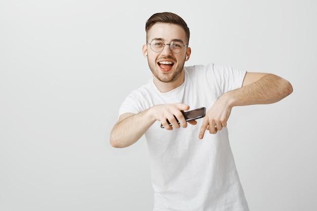 手に携帯電話を持つワイヤレスイヤホンで音楽に合わせて踊るメガネで幸せなハンサムな男