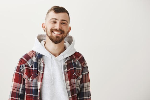 Счастливый красивый парень с бородой, улыбаясь доволен