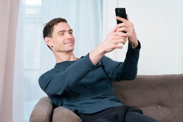 행복 잘 생긴 남자 젊은 남자 블로거는 침실에서 집에서 침대에 앉아 셀카 사진을 찍고있다