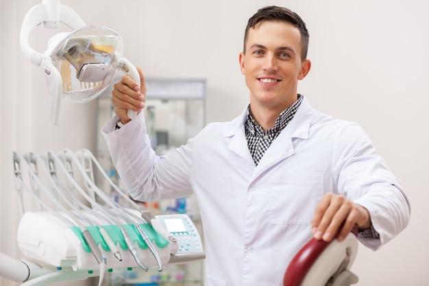 Счастливый красивый мужской стоматолог, радостно улыбаясь,