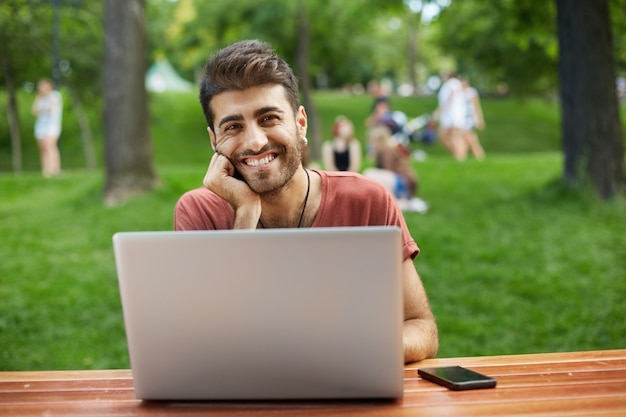 Happy handsome male developer, guy freelancer sit in park with laptop and smiling