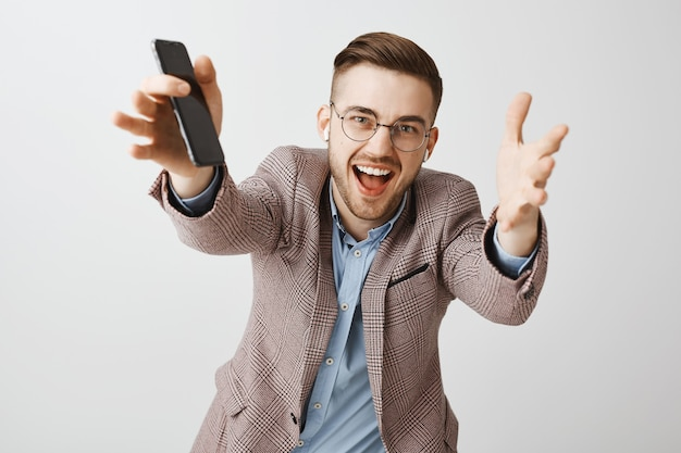 幸せなハンサムな男性起業家が手を伸ばし、携帯電話アプリでワイヤレスイヤホンとプレイリストで音楽を聴く