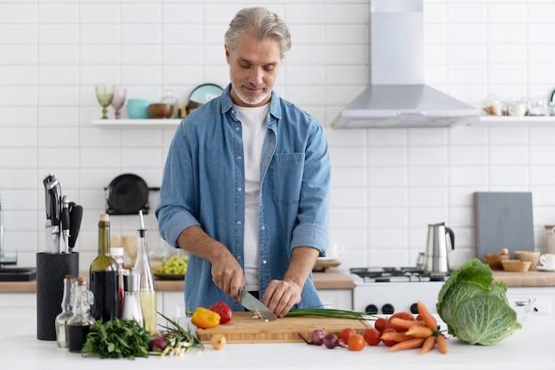 自宅のキッチンで料理をする幸せなハンサムな男