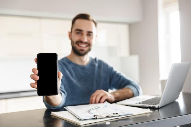 Счастливый красавец-фрилансер сидит за кухонным столом, работает на портативном компьютере, показывая пустой экран мобильного телефона