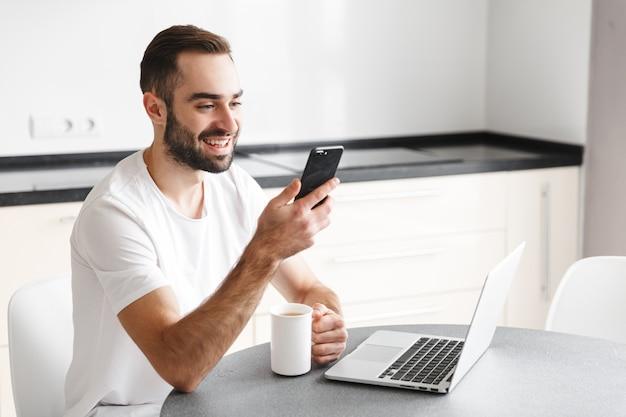 Счастливый красивый мужчина-фрилансер, сидя за кухонным столом, работая на портативном компьютере, используя мобильный телефон