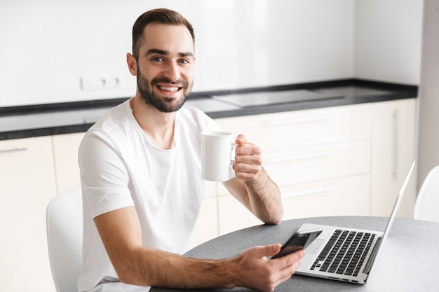 Happy handsome man freelancer sitting at the kitchen table, working on laptop computer, drinking coffee