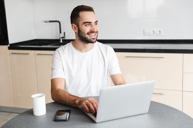 Happy handsome man freelancer sitting at the kitchen table, working on laptop computer