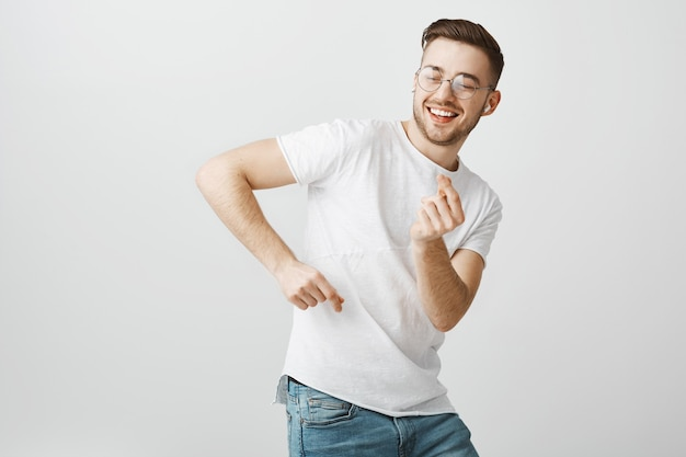 Happy handsome man in glasses dancing, listening music in wireless earphones