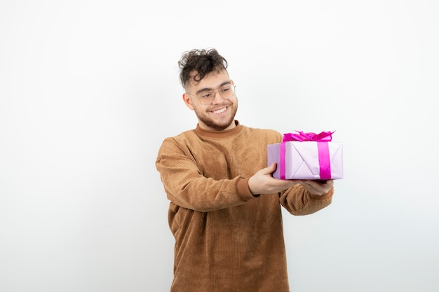 Happy handsome man holding his holiday gift over white.