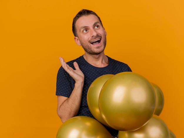 행복 잘 생긴 남자 헬륨 풍선을 보유하고 복사 공간이 오렌지 벽에 고립 된 측면을보고 제기 손으로 약자