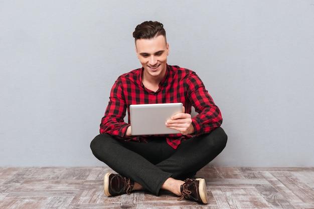 Счастливый красавец в рубашке, сидя на полу с таблеткой. изолированный серый фон