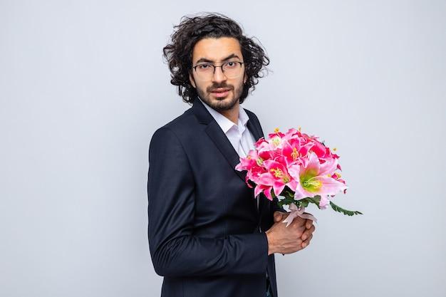 Счастливый красивый мужчина в костюме с букетом цветов, глядя в камеру, уверенно улыбается, празднует международный женский день 8 марта, стоя на белом фоне