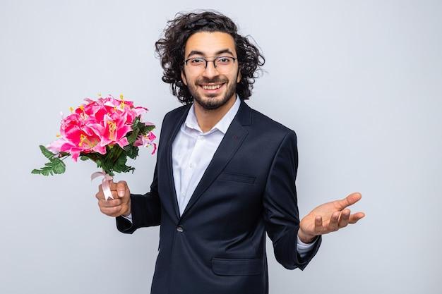 쾌활하게 웃는 찾고 꽃의 꽃다발과 양복에 행복 잘 생긴 남자