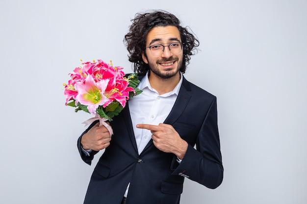 Счастливый красавец в костюме с букетом цветов, указывая на него указательным пальцем, глядя в камеру, весело улыбаясь, празднуя международный женский день 8 марта, стоя на белом фоне