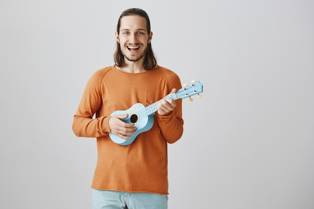Uomo bello felice che gioca ukulele e che canta