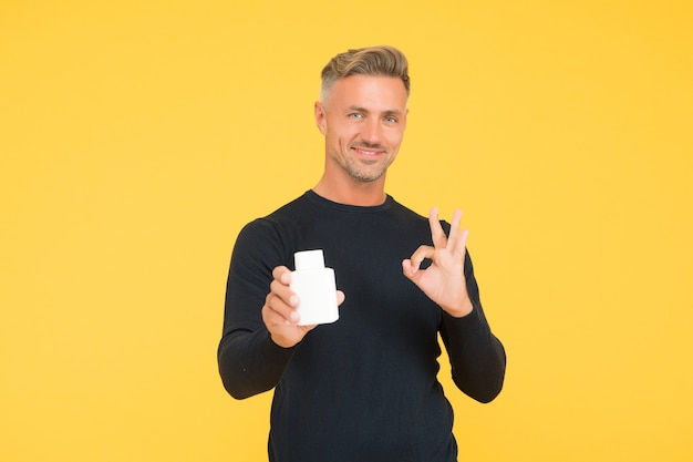 Happy handsome man show approval hand gesture presenting cosmetic product yellow background, ok.