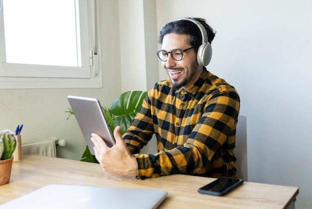 テーブルに座っている幸せなハンサムな男は、ヘッドフォン付きのタブレットを使用しています