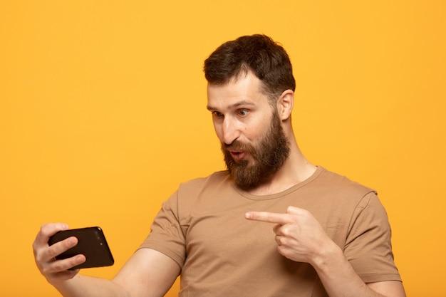 スマートフォンを使用して幸せなハンサムな男