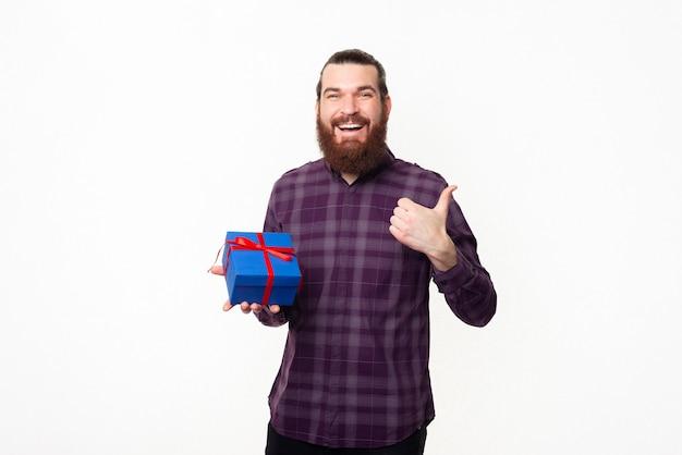 엄지 손가락을 보여주는 파란색 선물 상자를 들고 수염을 가진 행복 잘 생긴 남자
