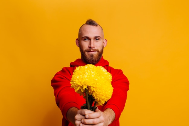 Happy handsome man with flowers bouquet of yellow asters