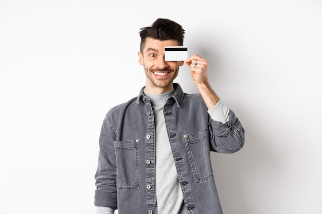Happy handsome man with moustache show plastic credit card on eye, smiling excited at camera, standing on white background.