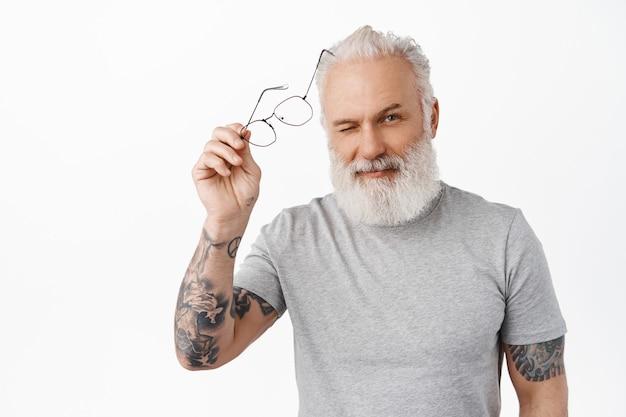 Felice bell'uomo maturo con barba e tatuaggi, togliersi gli occhiali e strizzare l'occhio sfacciato e fiducioso alla macchina fotografica, in piedi in maglietta grigia casual contro il muro bianco